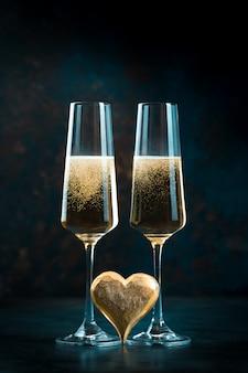 Due eleganti bicchieri romantici con scintillante champagne dorato con cuore dorato. concetto di san valentino