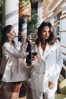 Due eleganti donne eleganti glamour sexy indossano abiti bianchi in un ristorante con un bicchiere di vino.