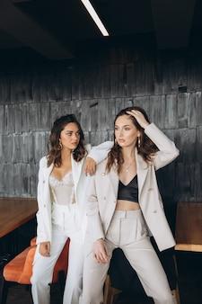 Due eleganti donne eleganti glamour sexy indossano abiti bianchi in un ristorante.