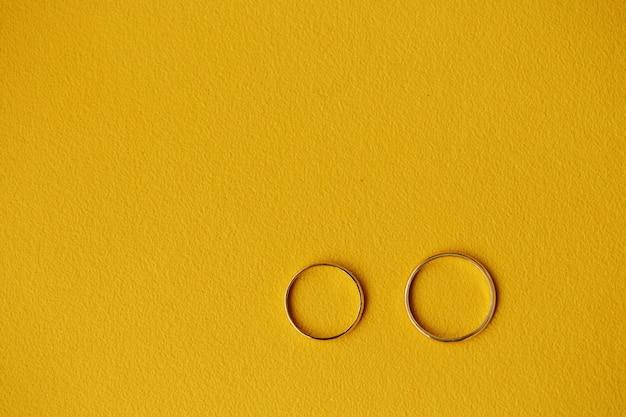Due fedi nuziali dorate su giallo
