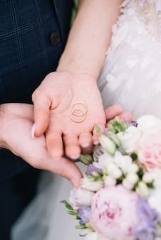 Due fedi nuziali nelle mani degli sposi fedi nuziali in argento fedi nuziali in metallo prezioso sulle mani di un uomo e una cerimonia di nozze di una donna.