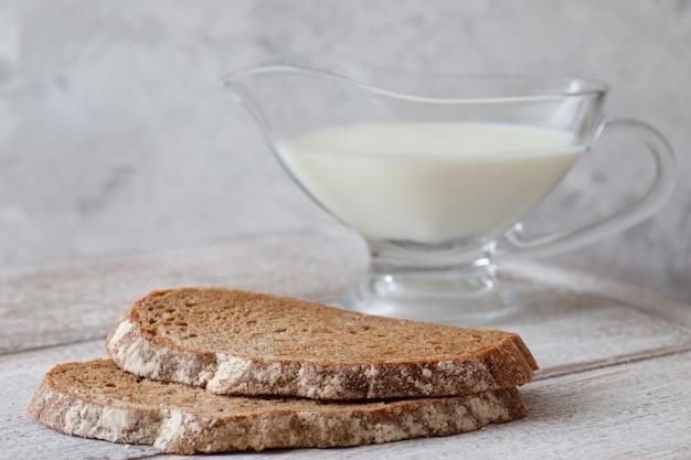 Due fette di pane scuro, una brocca di latte su un tavolo di legno e una grigia