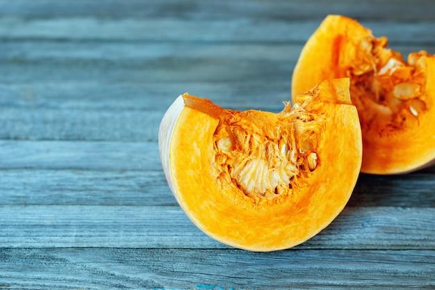Due fette di zucca arancione brillante su grigio