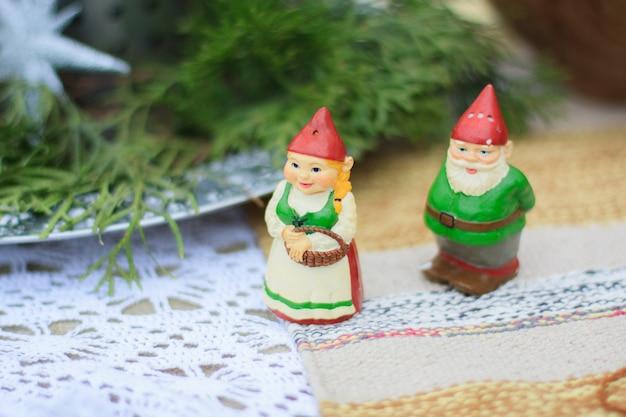 Due figure decorative in ceramica di gnomi verdi stanno su un tavolo