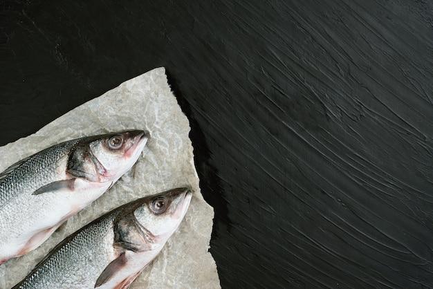 Due filetti di pesce crudo con spezie, erbe aromatiche, limone e sale su fondo di pietra nera