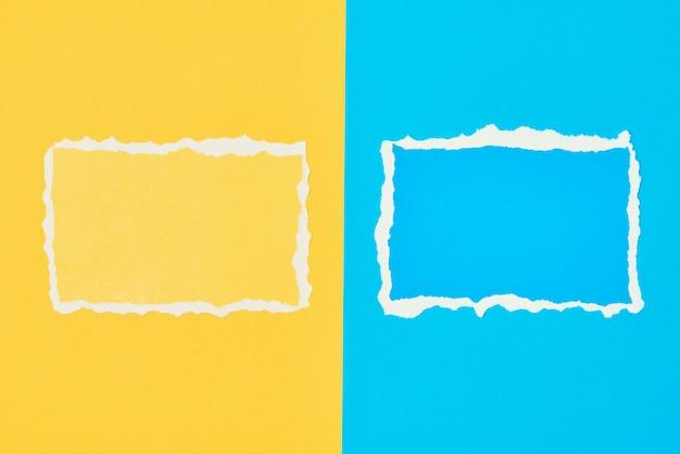 Due fogli di carta strappati bordo strappato su sfondo blu e giallo