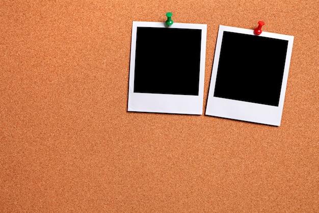 Due foto bianche appuntate su una tavola di sughero