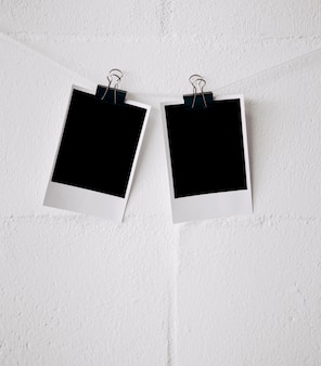 Due foto polaroid vuote attaccate alla stringa con le graffette del bulldog contro la parete