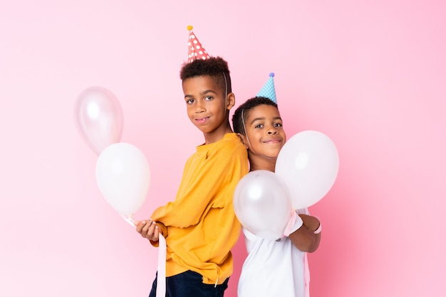 Due fratelli afroamericani che tengono i palloni sopra la parete rosa isolata