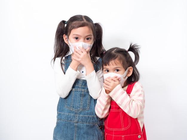 Due fratelli asiatici di una bambina carina che indossano una maschera igienica e che si coprono la bocca con la mano per proteggere diffondono il virus, l'influenza fredda o l'inquinamento.