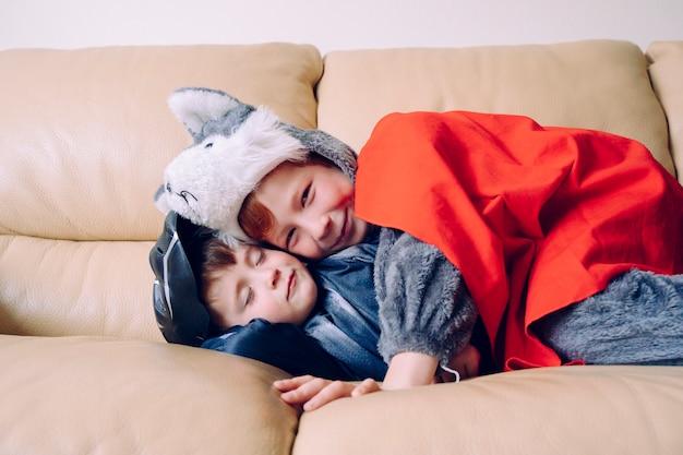 Due fratelli che dormono e si divertono sul divano bianco sognando con supereroi. concetto di unità familiare.