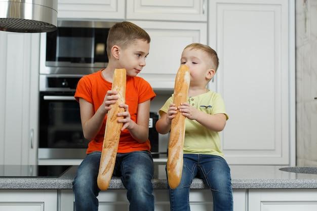 Due fratelli fanno colazione in cucina. ragazzi divertenti che mangiano un panino in cucina. bambino carino mangiare baguette.