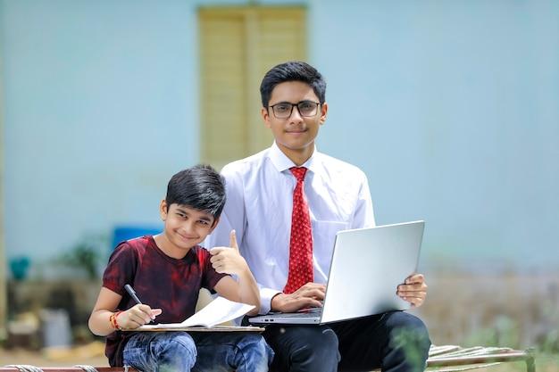 Due fratelli indiani utilizzando laptop, concetto di formazione online