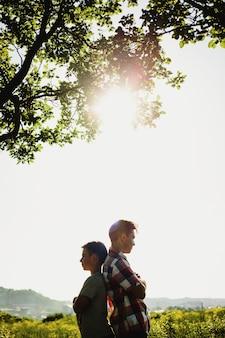 Due fratelli o amici stanno in piedi di fianco sotto l'albero verde nei raggi del sole della sera