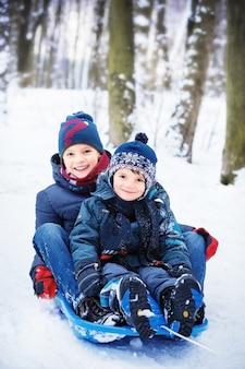 Due fratelli sulla slitta nella neve