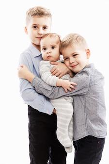 Due fratelli tengono in braccio un neonato. amore e tenerezza in famiglia.