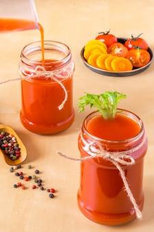 Due frullati di pomodoro in barattoli di vetro con gli ingredienti per la sua preparazione