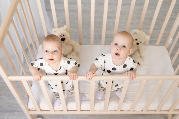 Due gemelli fratello e sorella di 8 mesi si siedono in pigiama nella culla e guardano la telecamera, vista dall'alto