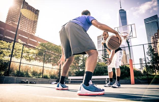 Due giocatori di basket di strada che giocano duro sul campo