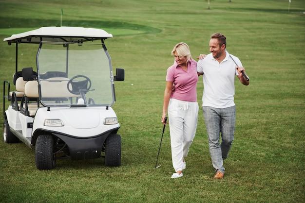 Due giocatori di golf, una donna e un uomo, vanno insieme alla buca successiva. uno studente va con il suo personal trainer ed è soddisfatto del suo successo nello sport