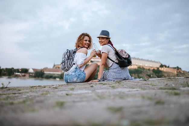 Due giovane donna elegante brindando seduti sulla banchina. guardando la fotocamera