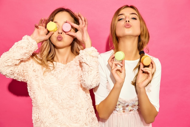 Due giovani affascinanti belle donne sorridenti hipster in abiti estivi alla moda. donne che producono occhiali, occhiali con amaretti colorati, che tengono macaron sul posto degli occhi. in posa sul muro rosa