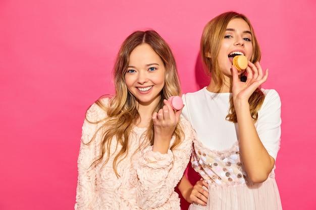 Due giovani affascinanti belle donne sorridenti hipster in abiti estivi alla moda. le donne con amaretti colorati, tenendo macarons vicino al viso. in posa sul muro rosa
