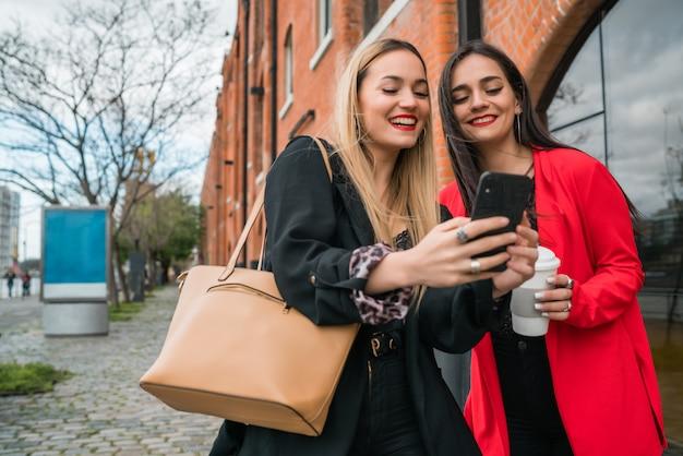Due giovani amici che utilizzano il loro telefono cellulare all'aperto.