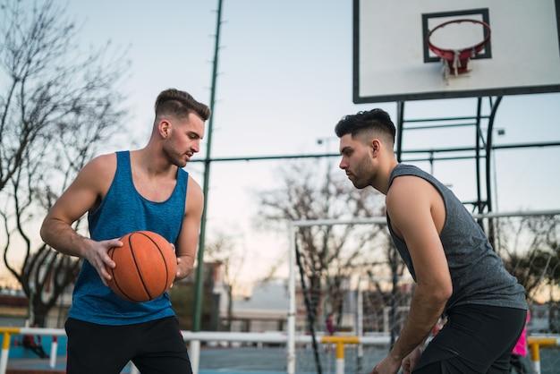 Due giovani amici giocando a basket.