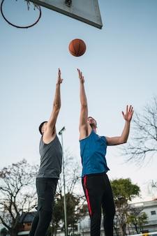 Due giovani amici giocando a basket