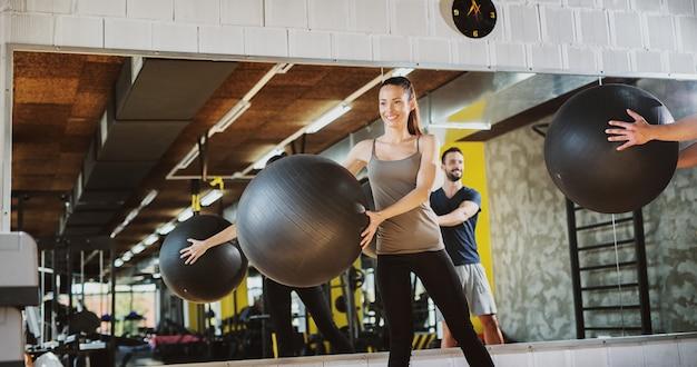 Due giovani bei che utilizzano le palle dei pilates per l'esercizio in una palestra.