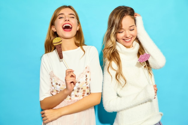 Due giovani bella donna che canta con microfono falso puntelli. donne alla moda in abiti estivi casual. linguaggio del corpo positivo di emozione femminile di espressione facciale con le grandi labbra. modelli divertenti isolati su blu