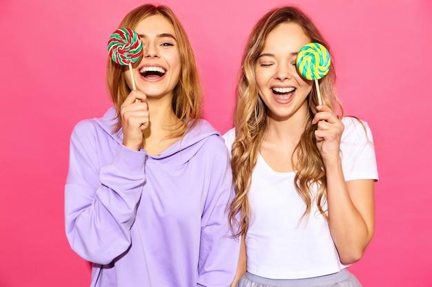 Due giovani belle donne bionde sorridenti dei pantaloni a vita bassa in vestiti alla moda di estate. donne calde spensierate che posano vicino alla parete rosa. i modelli positivi coprono gli occhi di lecca-lecca