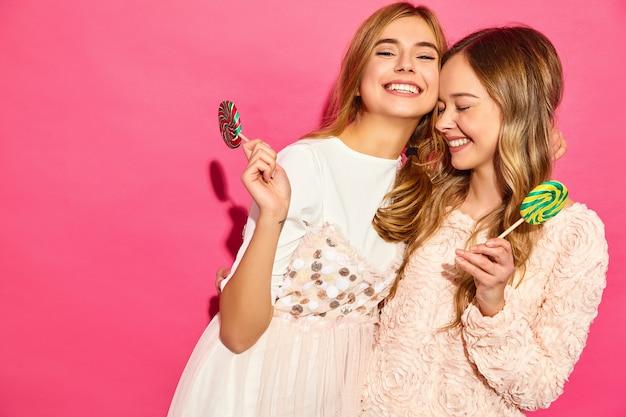 Due giovani belle donne bionde sorridenti dei pantaloni a vita bassa in vestiti alla moda di estate. donne calde spensierate che posano vicino alla parete rosa. modelli divertenti positivi che abbracciano con la lecca-lecca
