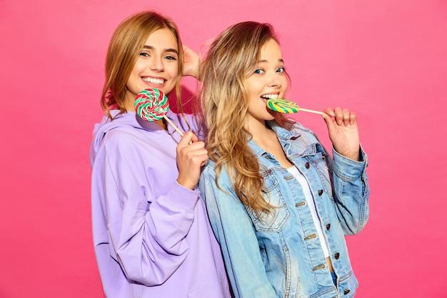 Due giovani belle donne bionde sorridenti dei pantaloni a vita bassa in vestiti alla moda di estate. donne calde spensierate che posano vicino alla parete rosa. modelli divertenti positivi con lecca-lecca