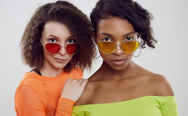 Due giovani belle donne in abiti estivi e occhiali da sole luminosi