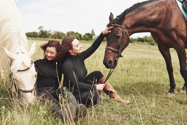 Due giovani belle donne in marcia per cavalcare vicino ai loro cavalli. loro amano gli animali