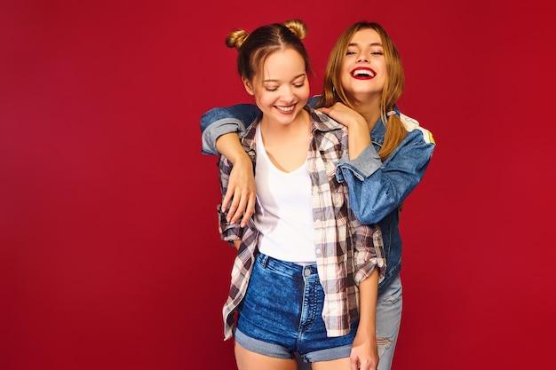 Due giovani belle donne sorridenti bionde dei pantaloni a vita bassa che posano in vestiti a quadretti della camicia dell'estate d'avanguardia