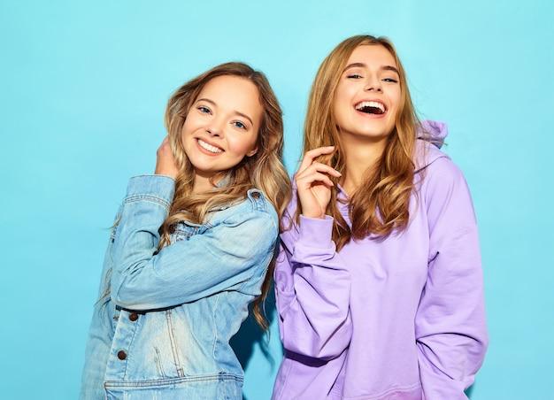 Due giovani belle donne sorridenti bionde dei pantaloni a vita bassa in vestiti d'avanguardia di estate. donne spensierate sexy che posano vicino alla parete blu in occhiali da sole. i modelli positivi impazziscono