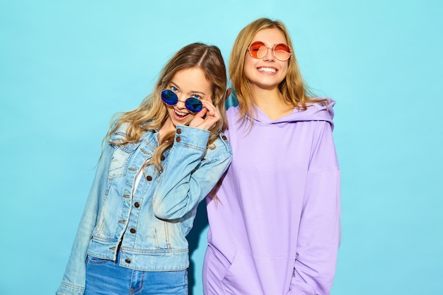 Due giovani belle donne sorridenti bionde dei pantaloni a vita bassa in vestiti d'avanguardia di estate. donne spensierate sexy che posano vicino alla parete blu in occhiali da sole. modelli positivi che impazziscono e si abbracciano