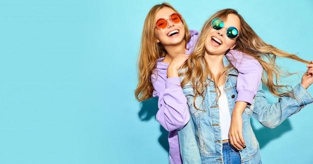 Due giovani belle donne sorridenti bionde dei pantaloni a vita bassa in vestiti d'avanguardia di estate. donne spensierate sexy che posano vicino alla parete blu in occhiali da sole. modelli positivi