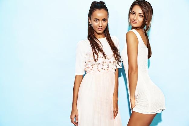 Due giovani belle donne sorridenti calde dei pantaloni a vita bassa in vestiti estivi d'avanguardia. donne spensierate sexy che posano vicino alla parete blu. modelli positivi