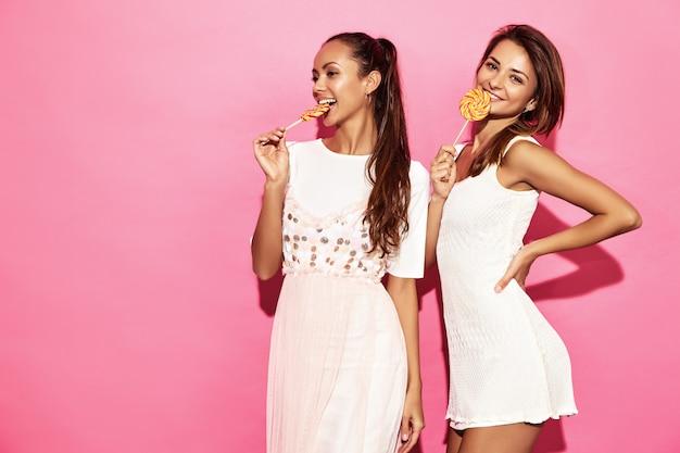 Due giovani belle donne sorridenti calde dei pantaloni a vita bassa in vestiti estivi d'avanguardia. donne spensierate sexy che posano vicino alla parete rosa. modelli positivi con lecca-lecca