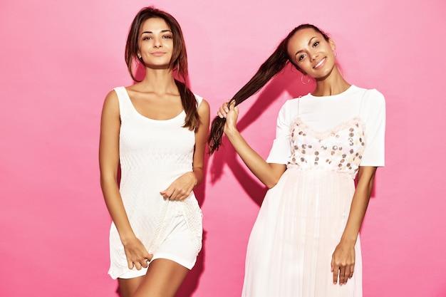 Due giovani belle donne sorridenti calde dei pantaloni a vita bassa in vestiti estivi d'avanguardia. donne spensierate sexy che posano vicino alla parete rosa. modelli positivi