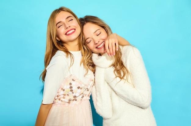 Due giovani belle donne sorridenti dei pantaloni a vita bassa in vestiti bianchi alla moda di estate. donne spensierate sexy che posano vicino alla parete blu. abbracciare modelli positivi