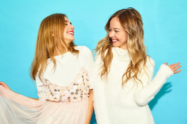 Due giovani belle donne sorridenti dei pantaloni a vita bassa in vestiti bianchi alla moda di estate. donne spensierate sexy che posano vicino alla parete blu. modelli positivi