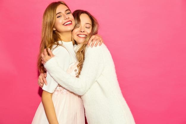 Due giovani belle donne sorridenti dei pantaloni a vita bassa in vestiti bianchi alla moda di estate. donne spensierate sexy che posano vicino alla parete rosa. abbracciare modelli positivi