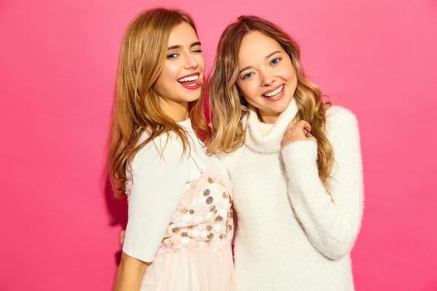 Due giovani belle donne sorridenti in abiti bianchi alla moda estate