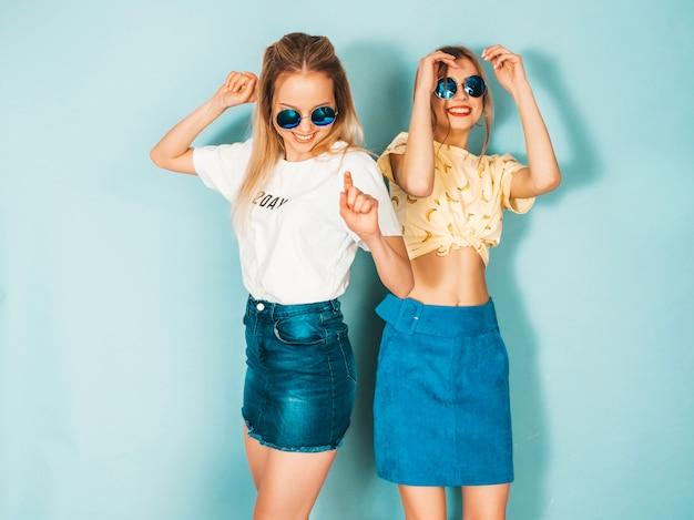 Due giovani belle ragazze bionde sorridenti dei pantaloni a vita bassa in gonne d'avanguardia dei jeans dell'estate vestiti.