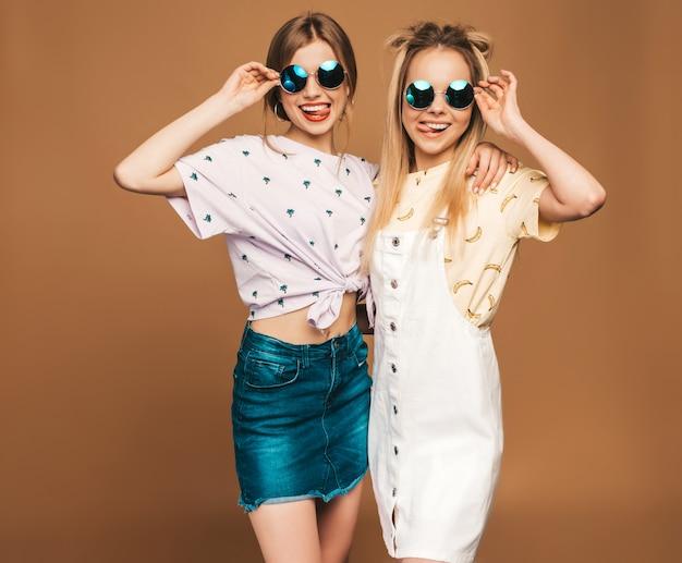Due giovani belle ragazze bionde sorridenti dei pantaloni a vita bassa in vestiti variopinti della maglietta di estate alla moda. donne spensierate sexy che posano sul fondo beige in occhiali da sole rotondi. modelli positivi che si divertono e mostrano